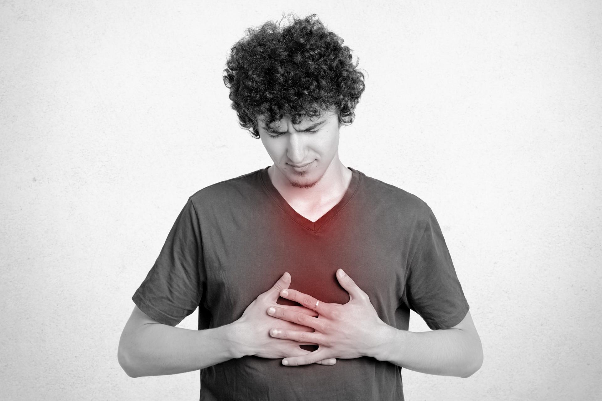 Ragazzo si comprime il petto con espressione contrita perché ha disturbi da reflusso gastrico.
